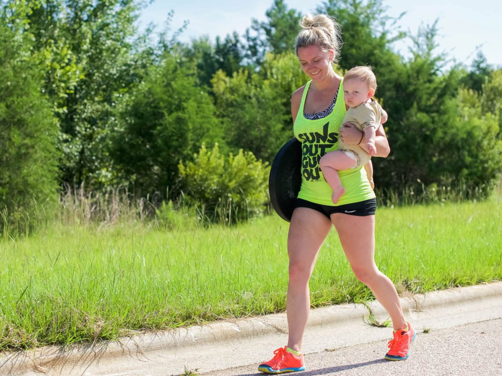 A smiling mother in colorful clothing carries a 25-lb. plate and a toddler during an outdoor CrossFit workout.