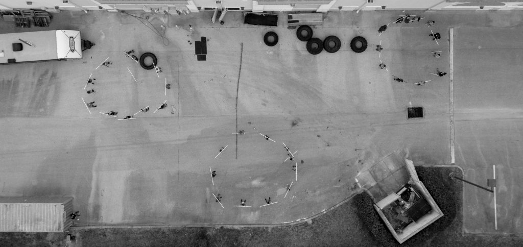 An overhead shot of circles of athletes practicing movement in a parking lot outside a CrossFit gym.