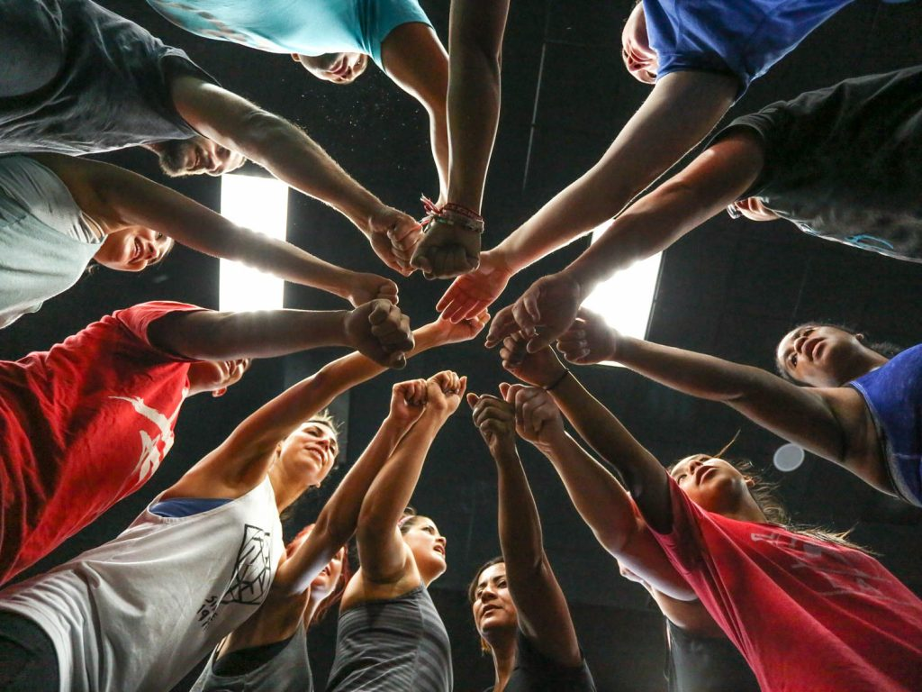 A photo taken from below a circle of athletes who are all reaching their hands into the center as part of a cheer.