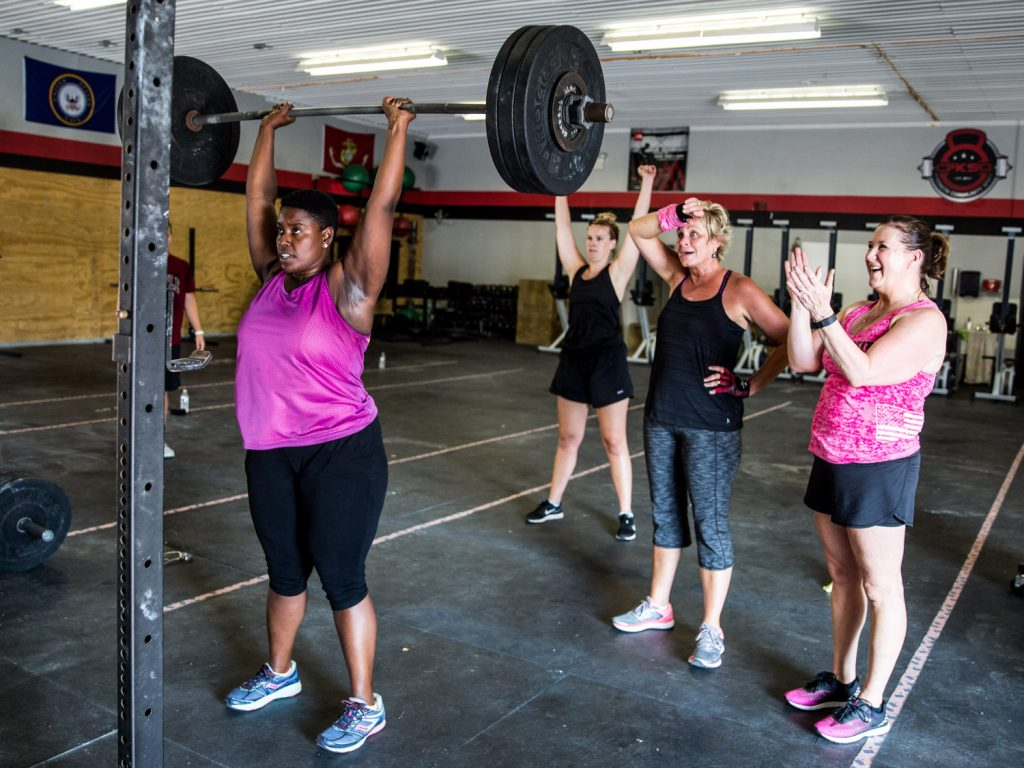 A woman holds a heavy barbell overhead in a CrossFit gym while several other women behind her cheer for her accomplishment.
