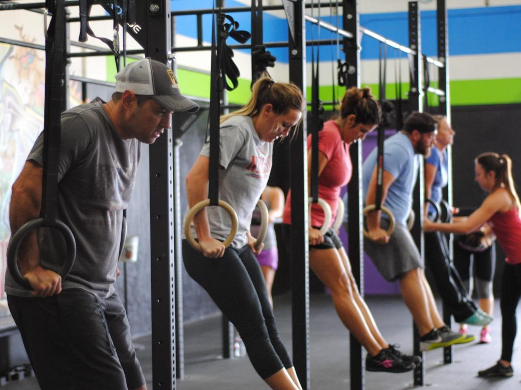 A varied group of people work on ring supports on a rig at a CrossFit gym.