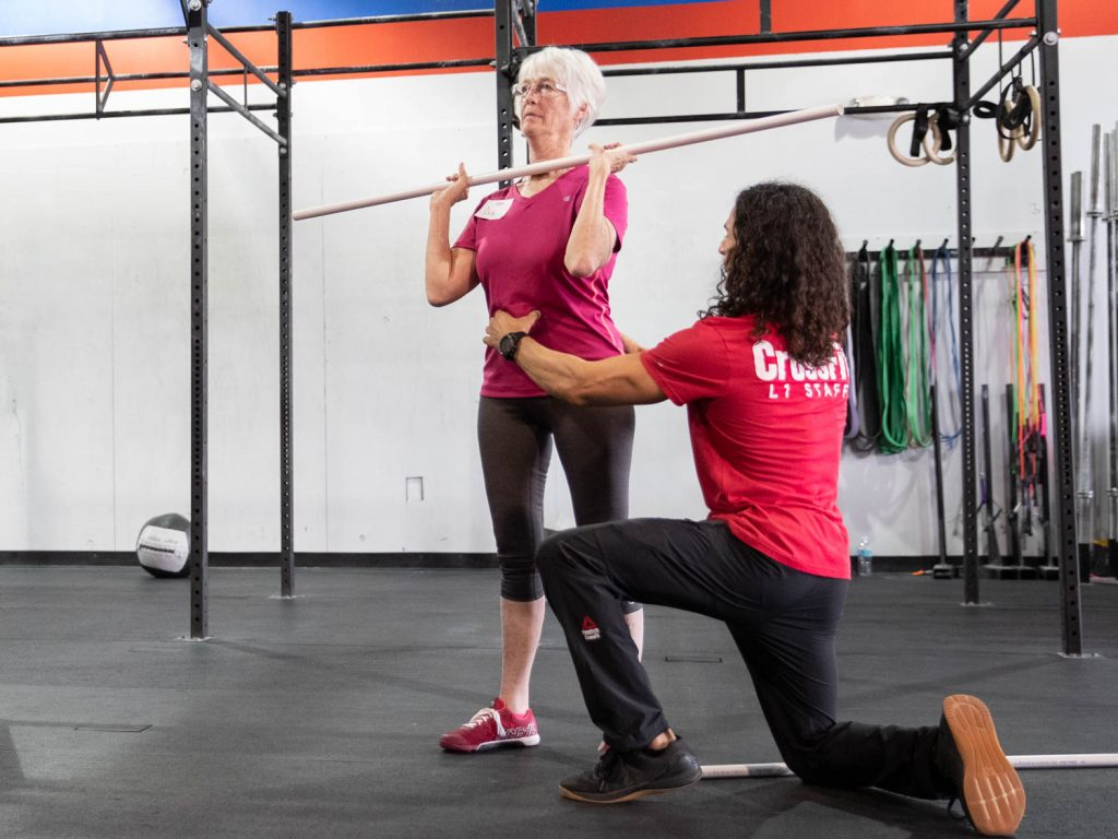 An older woman holds a PVC pipe in the front rack before a shoulder press while a CrossFit trainer cues her to engage her core muscles.