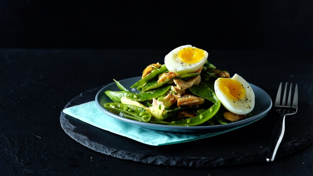 Salmon salad, presented on a dark plate and served with baby spinach, a boiled egg and avocado.