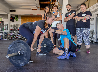 An athlete holds the deadlift set-up position and is cued to improved mechanics by a Seminar Staff member.