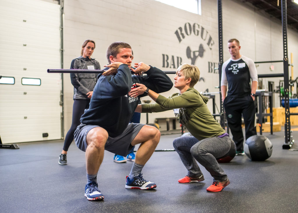 A man performs a front squat while a coach holds her hands under his elbows to encourage him to raise them into the proper position.