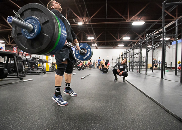A man with a loaded barbell hits triple extension in a clean while a Level 2 instructor observes from the side.