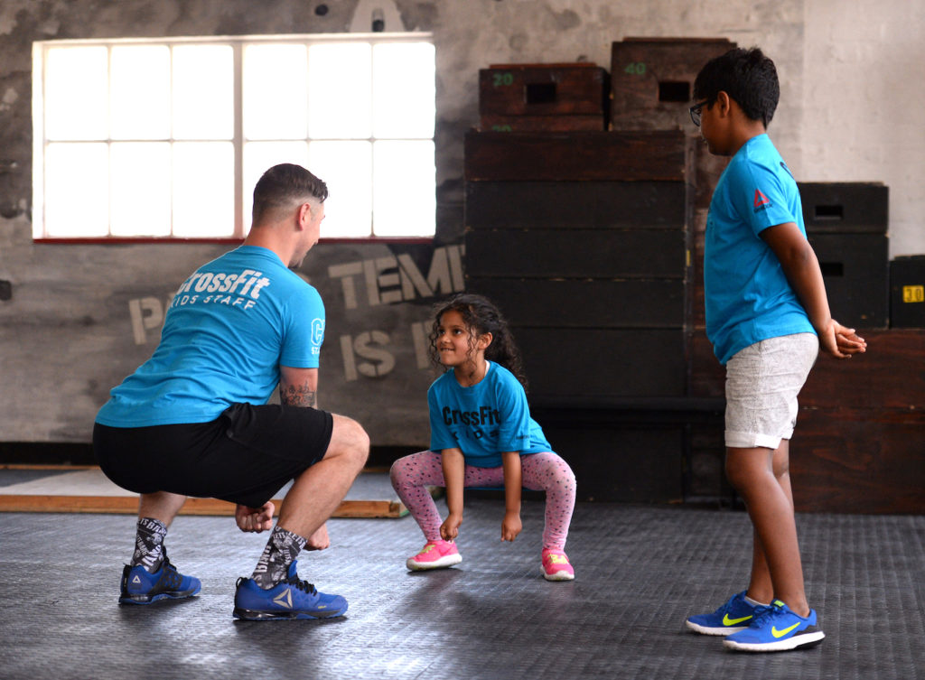 A CrossFit Kids Seminar Staff member instructs four children on the proper mechanics of an air squat, a foundational CrossFit movement.