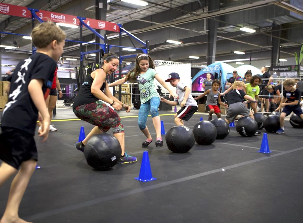A CrossFit Kids Seminar Staff member coaches adolescents through a burpee as part of a fun conditioning workout.