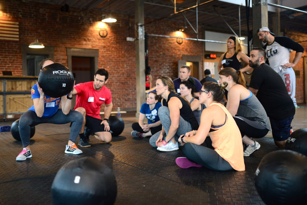 A small group of prospective CrossFit trainers and athletes observe a fellow aspiring trainer learn the fundamentals of the press with PVC as a Level 1 Course instructor coaches her.