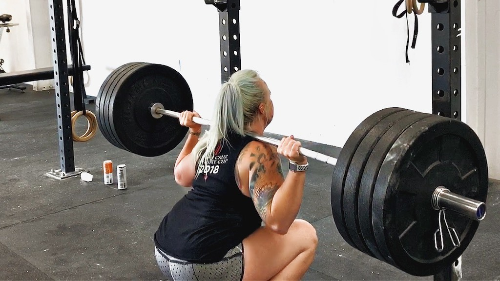 Woman completes an overhead lift - CrossFit and PTSD