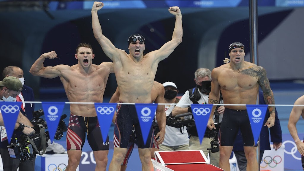 Olympic swimmer Zach Apple celebrating poolside in Tokyo.